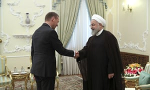 President Hassan Rouhani (right) shakes hands with French presidential envoy Emmanuel Bonne.