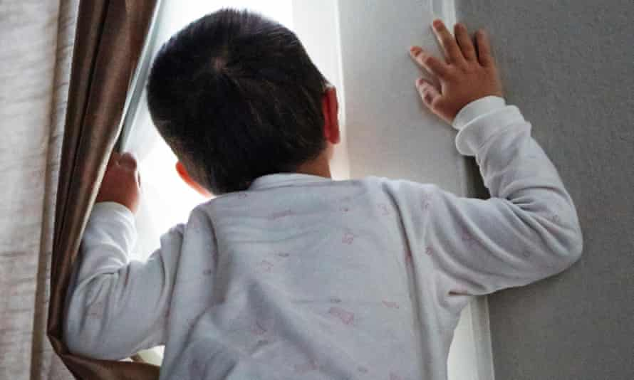 Boy peeking out from curtain