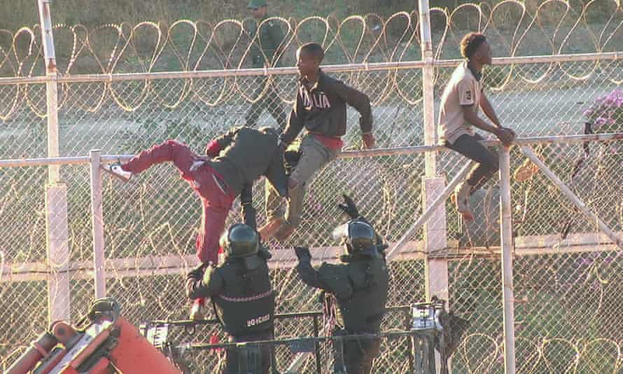 Police help people down from the the border fence between Morocco and Ceuta, Spain.