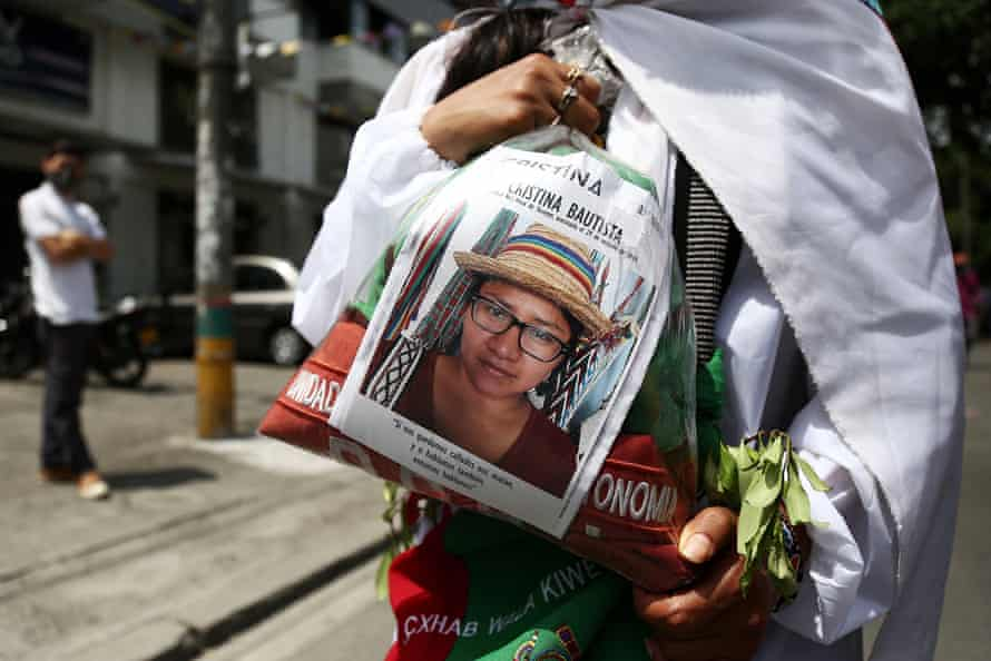 An indigenous woman shows a portrait of Cristina Bautista Taquinas, an indigenous leader killed by illegal armed groups, during a march in Cali, Colombia, last June.