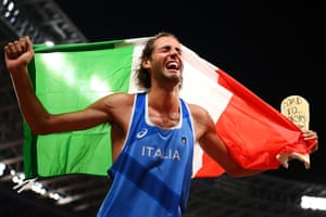 Gianmarco Tamberi of Italy celebrates after it was decided that he and Mutaz Essa Barshim of Qatar would share first place in the high jump final and each get a gold medal. He is holding a cast from an old injury on which is inscribed 'Road to Tokyo 2020, 2021'