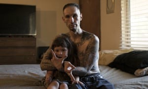 Sleepy flashes hand signs for the New Mexican prison gang 'Los Padillas' while his daughter sits on his lap.