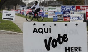A cyclist passes election signs near an early voting site in San Antonio, on 18 February 2020.