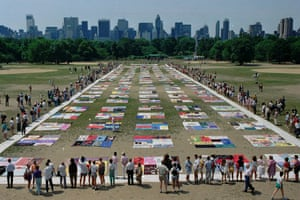 People watch as almost 1,500 quilt panels bearing the names of New York area residents who have died of AIDS are unfolded on the Great Lawn in New York's Central Park on 25 June 1988.