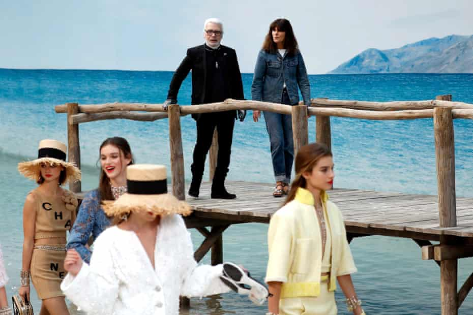 Karl Lagerfeld and Virginie Viard, a fashion studio director, watch as models present creations from his collection.