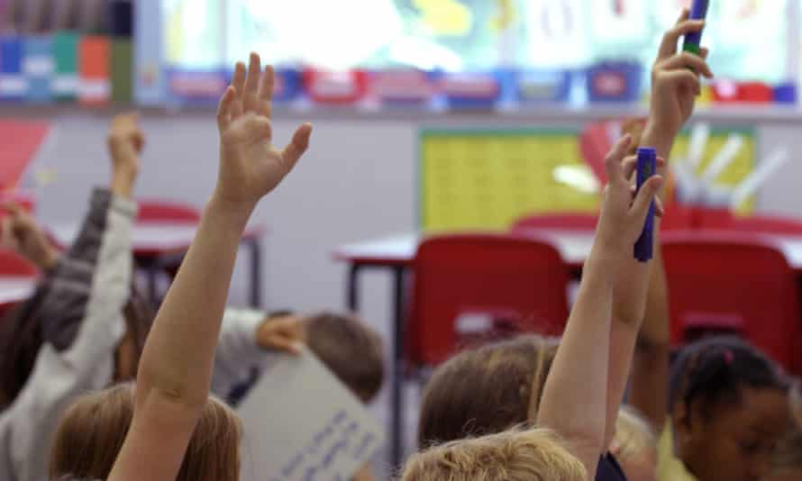 Children put their hands up during a lesson at a primary school