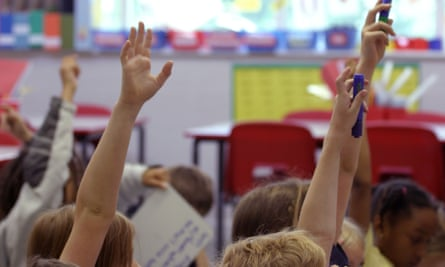 Children put their hands in the air during a lesson.