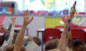 Schoolchildren raise their hands in the air