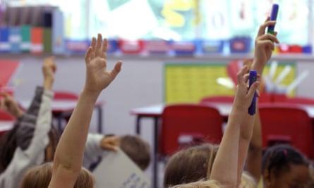 Schoolchildren raise their hands in the air