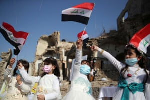 Mosul, Iraq: girls wave national flags as they gather at Church Square before the pope's arrival