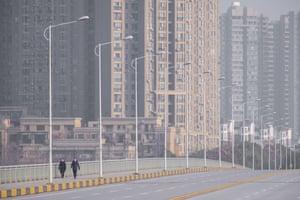 People wearing face masks walk down a deserted street in Wuhan