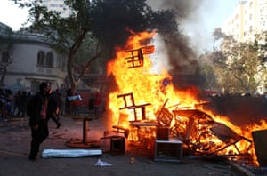 A demonstrator watches a burning barricade during a protest in Santiago, Chile, 12 November