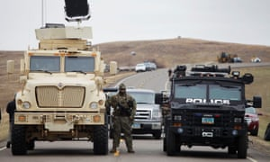 North Dakota law enforcement officers stands next to two armored vehicles just beyond the police barricade near a Dakota Access Pipeline construction site.