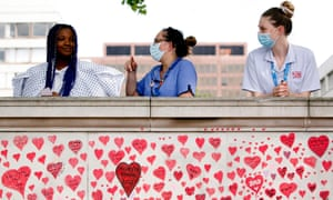 Medics stand above the National Covid Memorial Wall of hearts in London.