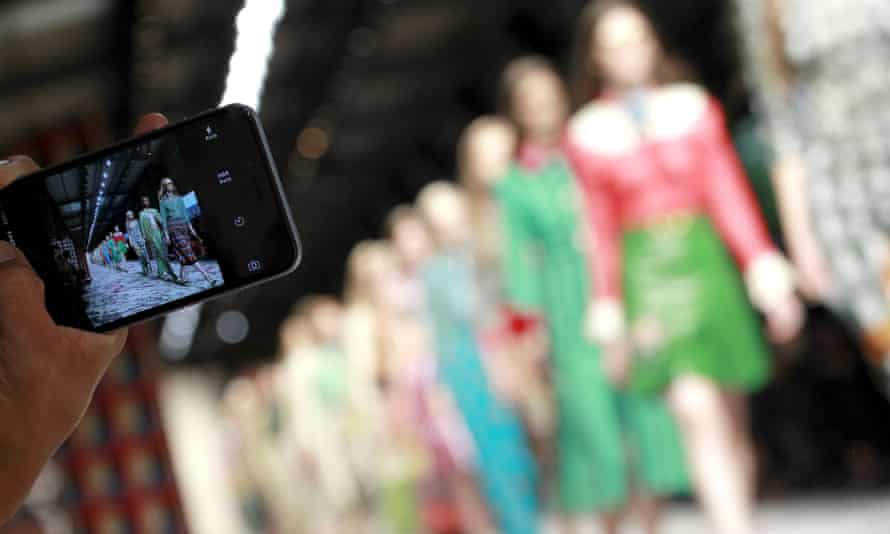 Guest takes picture at a fashion show.