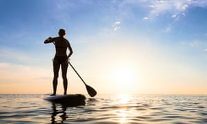 A woman on a paddleboard at sunset
