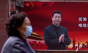 A woman wearing a protective mask in front of a portrait of President Xi Jinping, Shanghai.