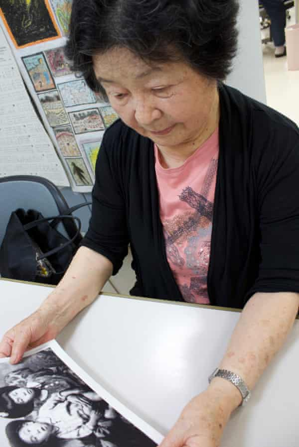 Hiroko Hatakeyama, a survivor of the Hiroshima atomic bombing, looks at a family photograph taken before the attack.