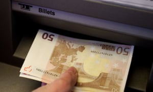 A British holidaymaker withdraws euro bank notes from a cash machine