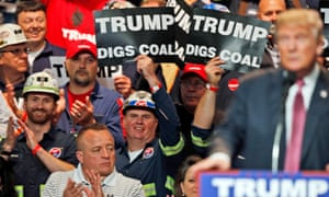 Coalminers wave signs as Donald Trump speaks at a Republican rally in Charleston, West Virginia.