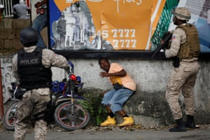 Port-au-Prince, Haiti: A man ducks from police officers during a march demanding the resignation of the Haitian president, Jovenel Moïse