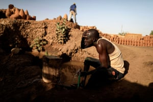 David Plantino, 35, a pottery maker from South Sudan, cools himself down with water from the Nile river, next to a workshop in an area known as the 'Potters Village'  in Omdurman, Sudan