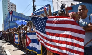 Cubans hold US and Cuban flags outside the US Embassy building.