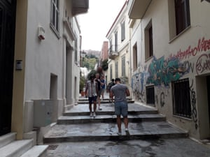 Tourists walking through the streets of ancient Plaka in Athens.