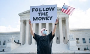 A man protests outside the supreme court in Washington during a case about releasing Donald Trump's tax returns this summer.