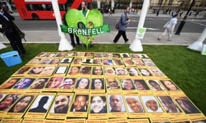 Demonstrators calling for justice for the victims of the Grenfell Tower fire stand with images of the dead on Parliament Square in London.