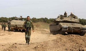 Israeli soldiers stand guard next to a tank