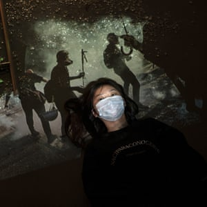 A protester, who identified herself as Morty, poses next to broken glass as a projector displays a photograph, taken during the unrest in Hong Kong.