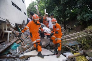 Rescue personnel evacuate earthquake survivor Ida, a food vendor, from the rubble of a collapsed restaurant.