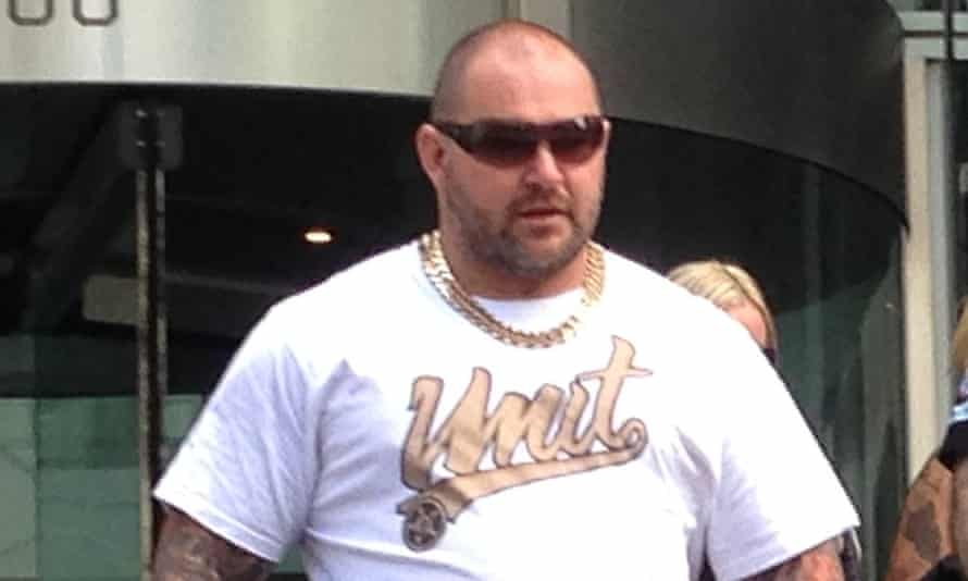 """man in sunglasses wearing a gold chain and white t-shirt saying """"unit"""""""