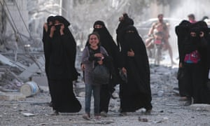 A girl walks with women who were evacuated by Syrian Democratic Forces fighters from the Isis-controlled city of Manbij, Syria.