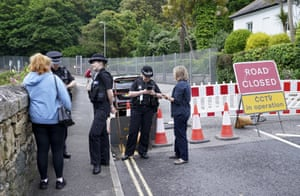 Police check the papers of residents at a checkpoint in St Ives