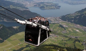 """People ride on the world's first open-air double-decker cable car system, the newly-built """"Cabrio"""", on the Stanserhorn mountain, near Lucerne"""