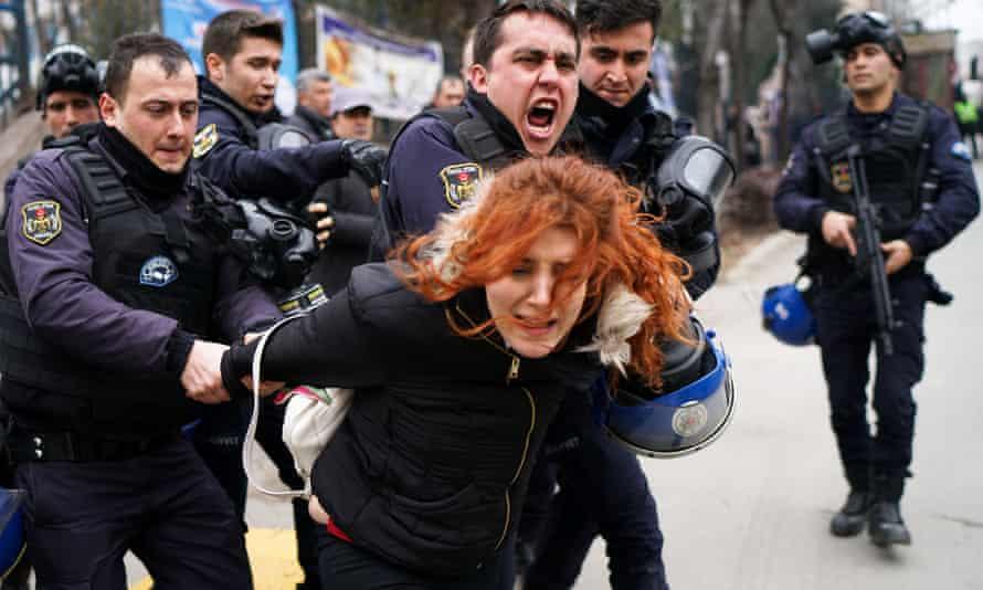 Riot police detain a demonstrator