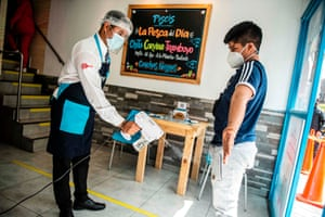 A waiter disinfects a customer at a restaurant in Lima, Peru. The country's restaurants were closed for four months due to the pandemic.