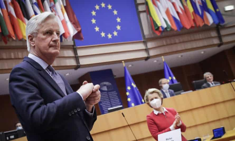 Michel Barnier standing with his hands clasped in the European parliaent, with the EU banner and a row of flags as a backdrop, with Ursula von der Leyen in a mask in the background