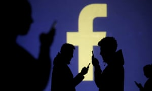 Silhouettes of mobile users are seen next to a screen projection of Facebook logo.