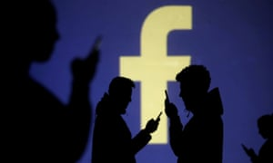 Silhouettes of mobile users are seen next to a screen projection of Facebook logo