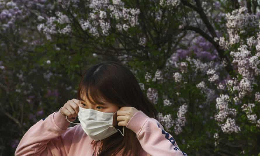 A Chinese woman puts on her protective mask while enjoying the spring weather in Beijing