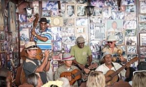 Musicians playing their instruments in front of a wall covered with photos at Casa de la Trova, Santiago de Cuba, Cuba.