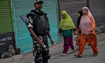 Kashmiri women walk past a soldier in Srinagar