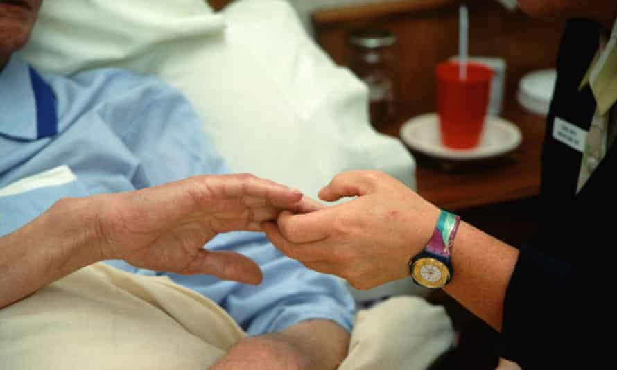 Hospice worker holding hand
