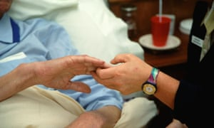 A hospice worker holds the hand of a patient.