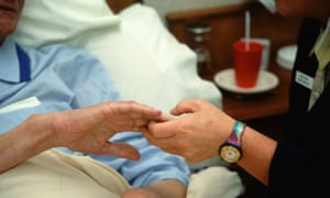 Hospice worker holding the hand of an elderly man.