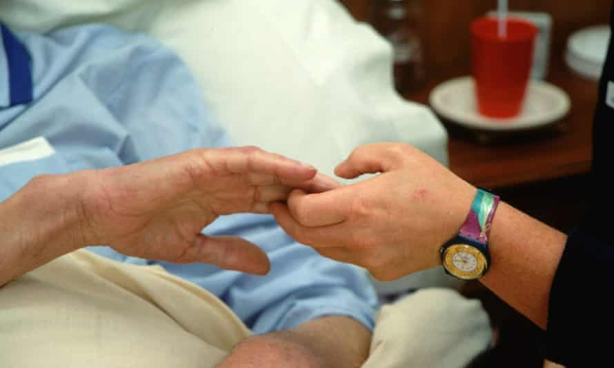 Hospice worker holding hand of patient
