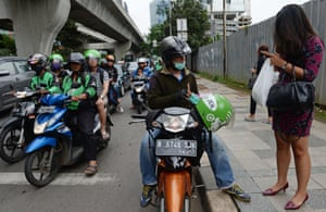 A motorcycle taxi for smartphone app Go-Jek picks up a customer.